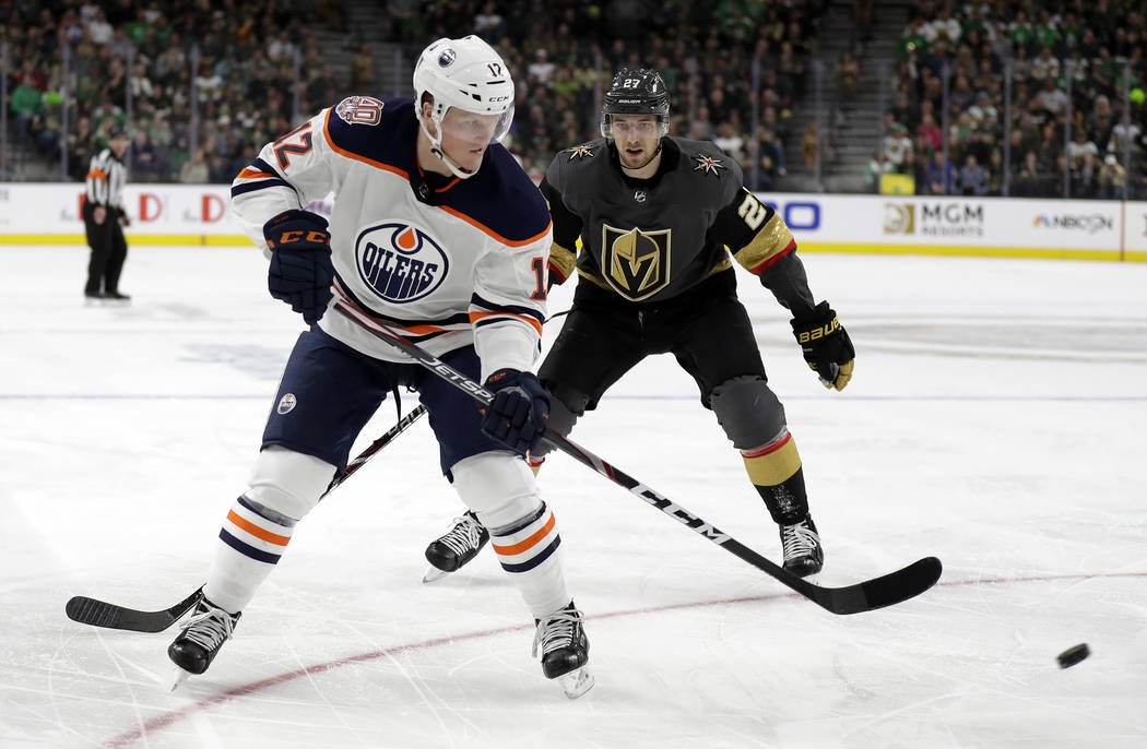 Edmonton Oilers center Colby Cave (12) takes a shot as Vegas Golden Knights defenseman Shea Theodore defends during the third period of an NHL hockey game Sunday, March 17, 2019, in Las Vegas. The ...