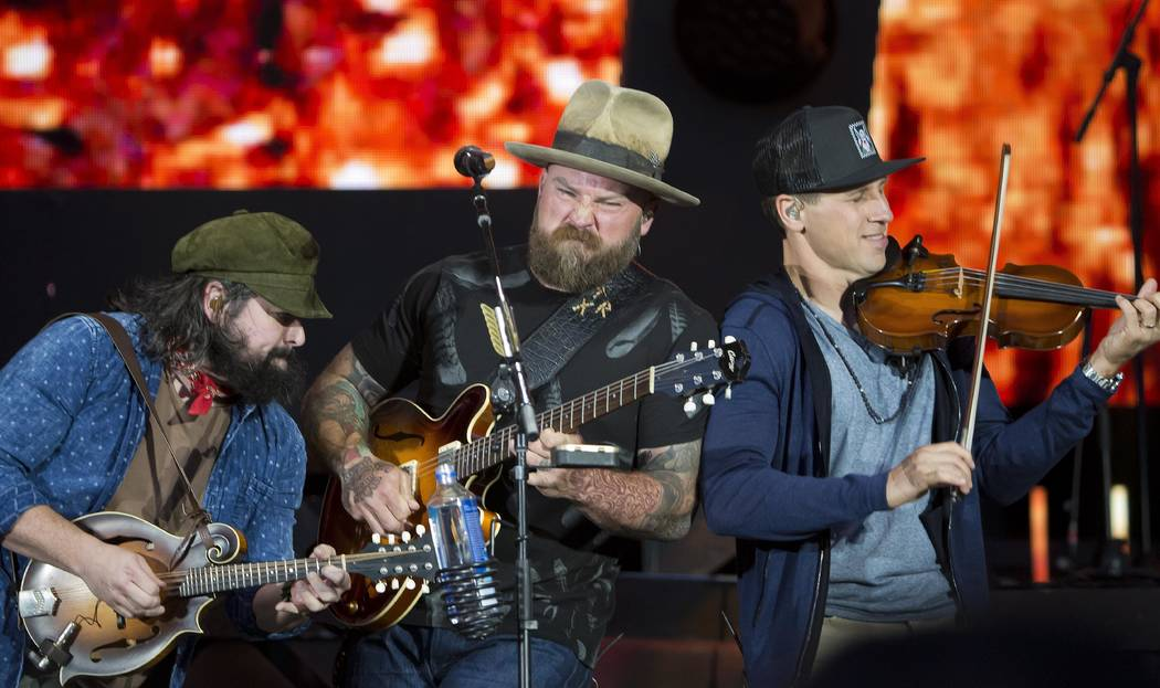 Coy Bowles, from left, Zac Brown and Jimmy De Martini of the Zac Brown Band perform at Fenway Park on Friday, June 15, 2018, in Boston. (Photo by Winslow Townson/Invision/AP)