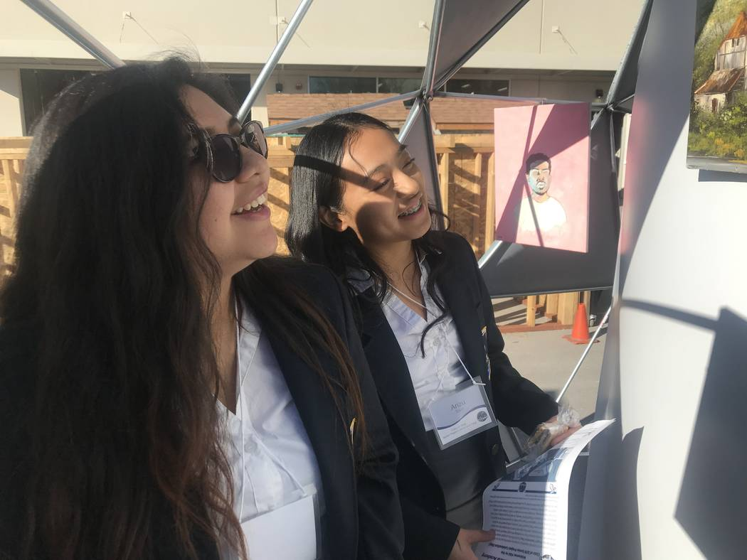 Odalys Jimenez, 17, (left)and Arizu Toriz, 16, stand in an art gallery at the school during the presenting of Capstone Projects at the East Career and Technical Academy on Friday, March 15. (Mia S ...