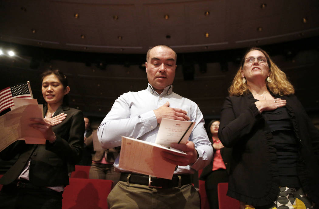 New U.S. citizens (from left) Supinya Phapant, of Thailand, Julio Martinez, of El Salvado,r and Mary McCarthy, of Canada, recite the Pledge of Allegiance during a naturalization ceremony at the Ge ...