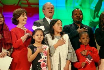 Former President George W. Bush and former first lady Laura Bush recite the pledge of allegiance with new U.S. citizens, including Felix Odeh, (top right) of Nigeria, during a naturalization cerem ...