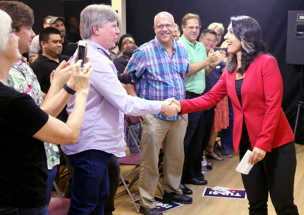Presidential hopeful U.S. Rep. Tulsi Gabbard, D-Hawaii, says hello to supporters, including Reilly Stephen, during a meet and greet at the Asian Culture Center in downtown Las Vegas Monday, March ...
