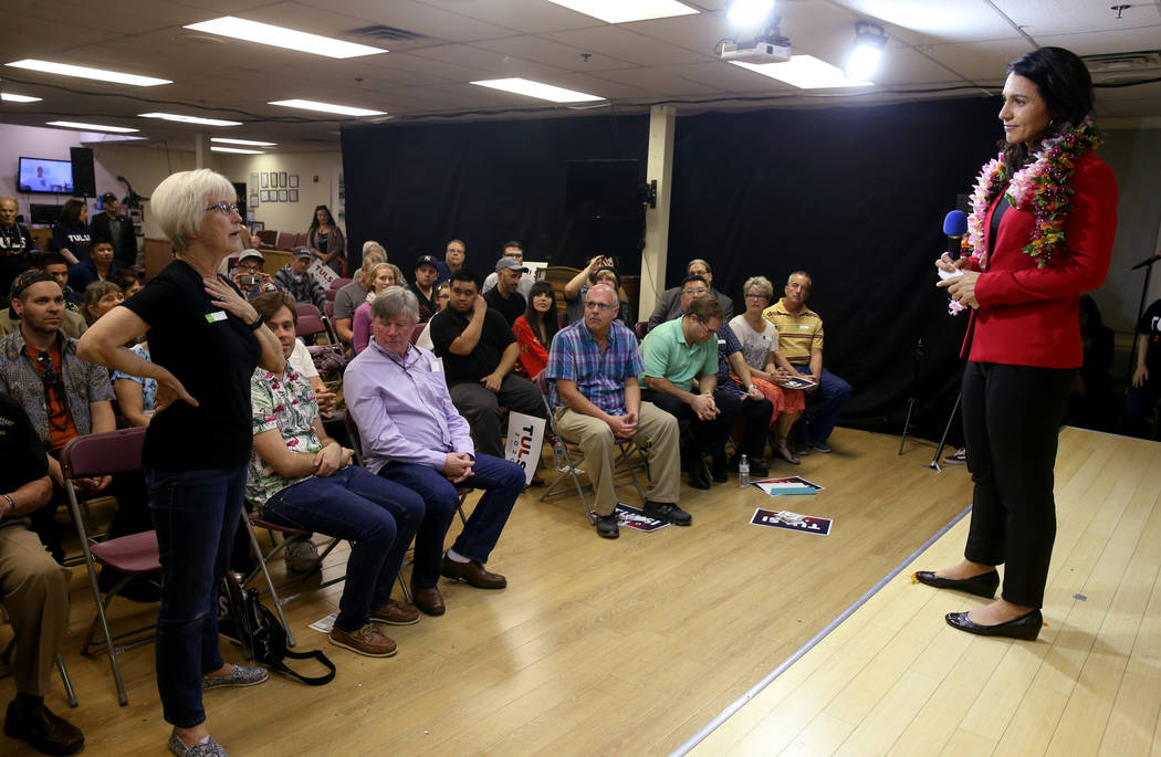Presidential hopeful U.S. Rep. Tulsi Gabbard, D-Hawaii, right, takes a questions from Mary Macioce, standing left, during a meet and greet at the Asian Culture Center in downtown Las Vegas Monday, ...