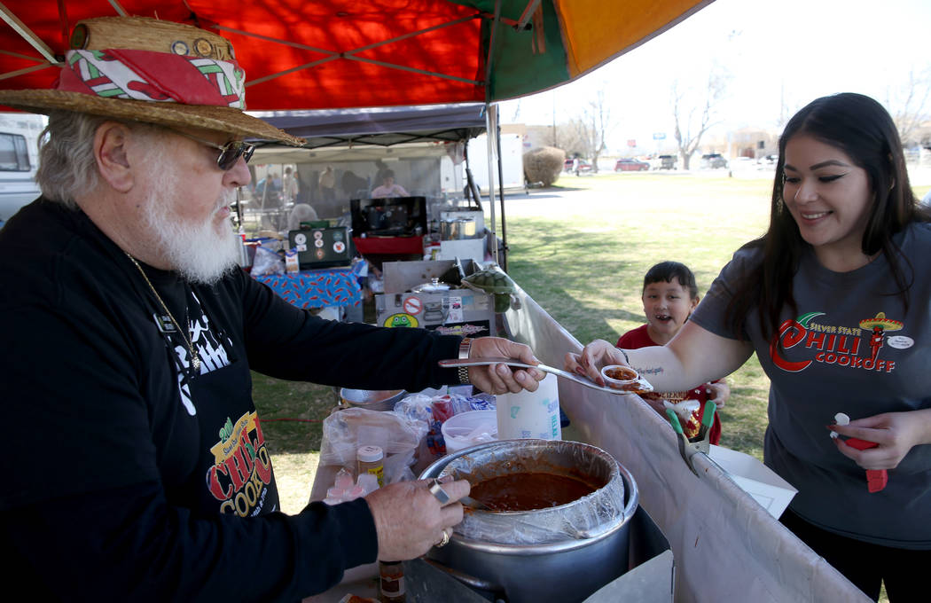 Mike Austin of San Bernardino, California, offers his People's Choice chili to Josie Kuezado and her daughter Alaiyah Brooks, 6, of Pahrump in his booth at the Nevada State Chili Cook-off at Petra ...