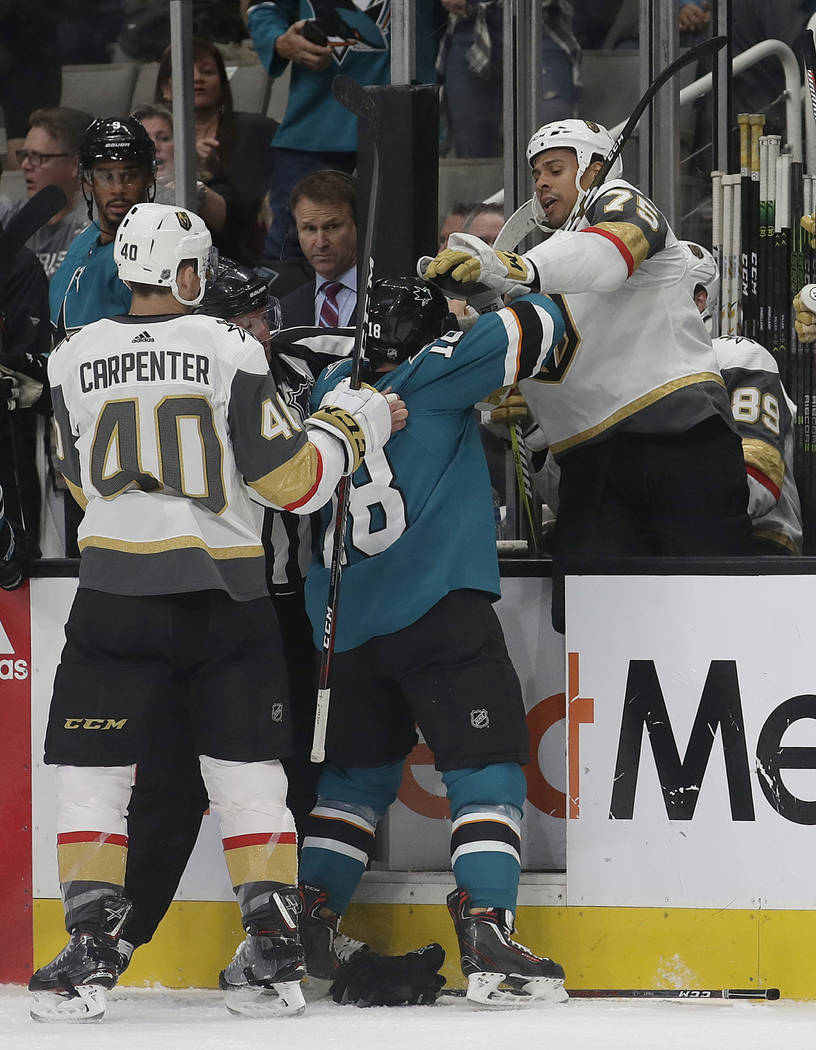 San Jose Sharks center Micheal Haley, center, goes after Vegas Golden Knights right wing Ryan Reaves (75) on the bench as center Ryan Carpenter (40) holds his jersey during the first period of an ...