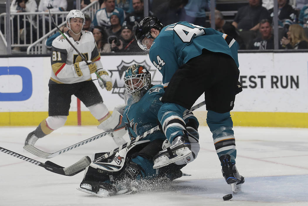 San Jose Sharks goaltender Aaron Dell, center, and defenseman Marc-Edouard Vlasic (44) look for the puck in front of Vegas Golden Knights center Jonathan Marchessault (81) during the second period ...