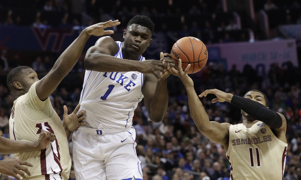 Duke's Zion Williamson, center, loses the ball as he is trapped by Florida State's David Nichols, right, and Raiquan Gray, left, during the first half of the NCAA college basketball championship g ...