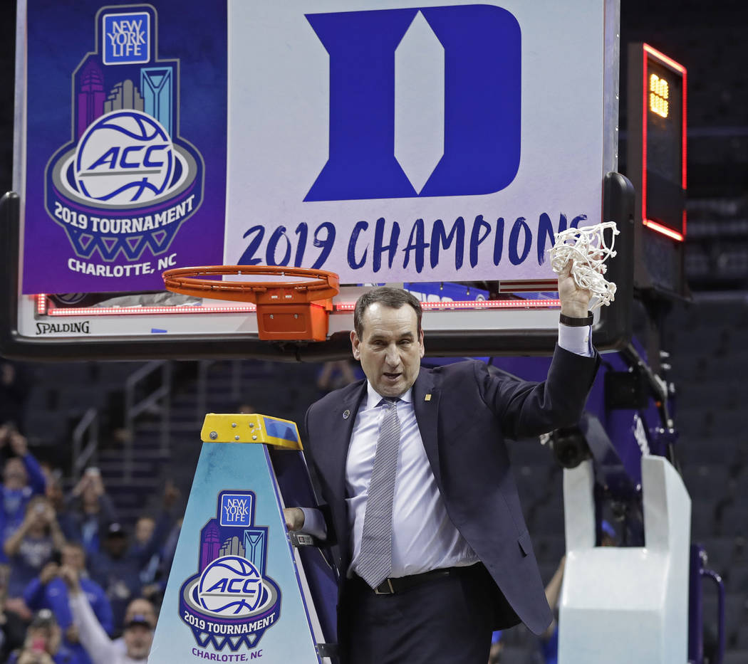 Duke head coach Mike Krzyzewski celebrates Duke's win over Florida State after cutting down a net after the NCAA college basketball championship game of the Atlantic Coast Conference tournament in ...