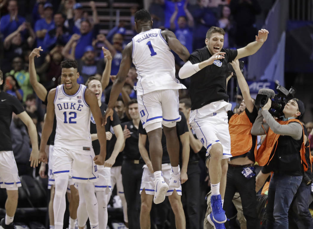 Duke players including Javin DeLaurier (12) and Zion Williamson (1) celebrate after defeating Florida State in the NCAA college basketball championship game of the Atlantic Coast Conference tourna ...