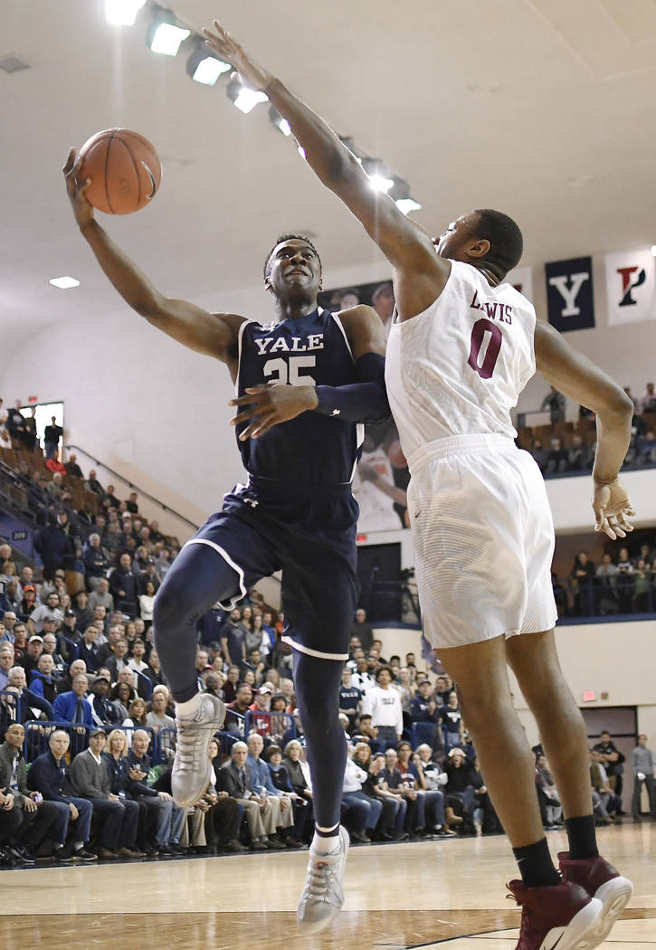 Yale's Miye Oni, left, shoots as Harvard's Chris Lewis, right, defends during the first half of an NCAA college basketball game in a for the Ivy League championship at Yale University in New Haven ...