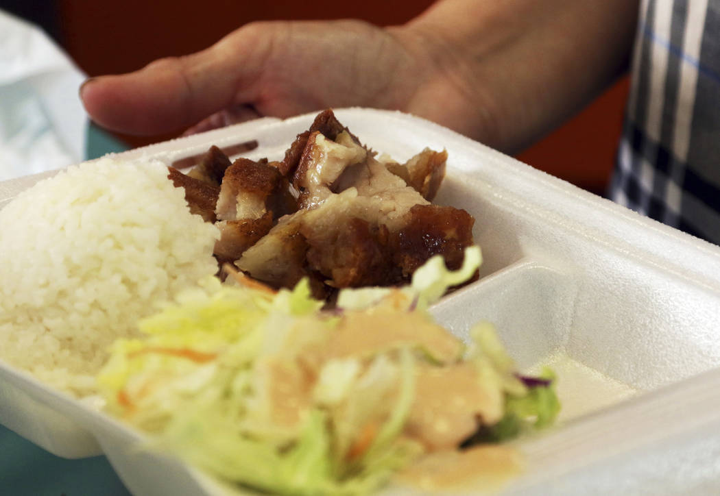 In this Thursday, March 14, 2019 photo, Belinda Lau, manager of the Wiki Wiki Drive Inn takeout restaurant in Honolulu, holds a polystyrene foam box containing an order of roast pork, rice and sal ...