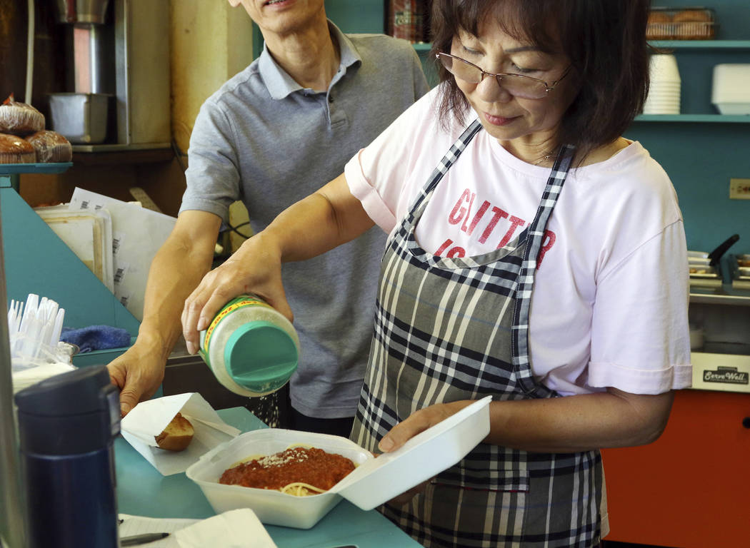 In this Thursday, March 14, 2019 photo, Belinda Lau, manager of the Wiki Wiki Drive Inn takeout restaurant in Honolulu, sprinkles cheese on an order of spaghetti in a styrofoam container. Hawaii w ...