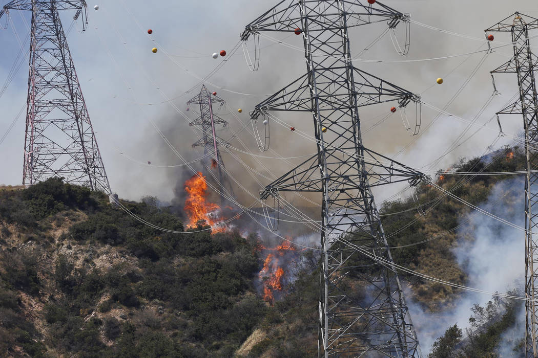 In this Monday, June 20, 2016 file photo, fires burn on a hillside near power lines outside Azusa, Calif., as wildfires erupted in Southern California during an intensifying heat wave stretching f ...
