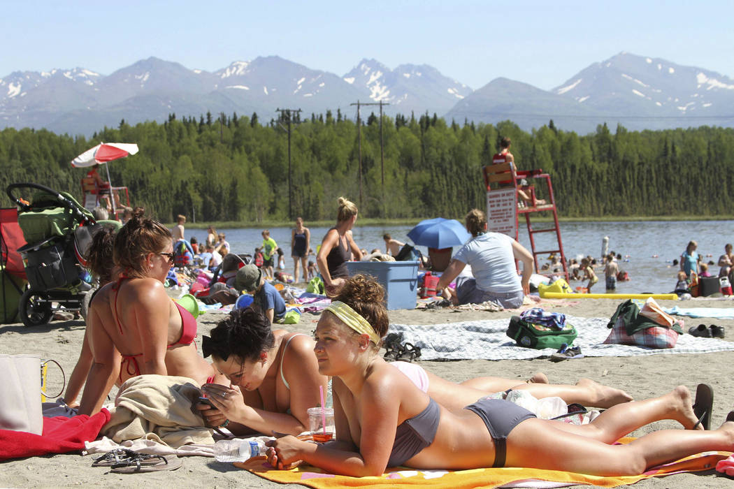 In this Monday, June 17, 2013 file photo, people sunbathe at Goose Lake in Anchorage, Alaska., as a heat wave continues across the state. Temperatures in the 80s and 90s are hot for the northernmo ...