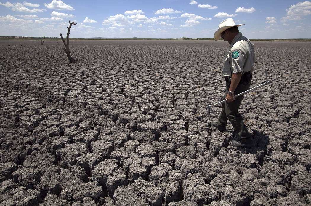 In this Aug 3, 2011 file photo, Texas State Park police officer Thomas Bigham walks across the cracked lake bed of O.C. Fisher Lake, in San Angelo, Texas. The impacts of record-breaking heat and y ...
