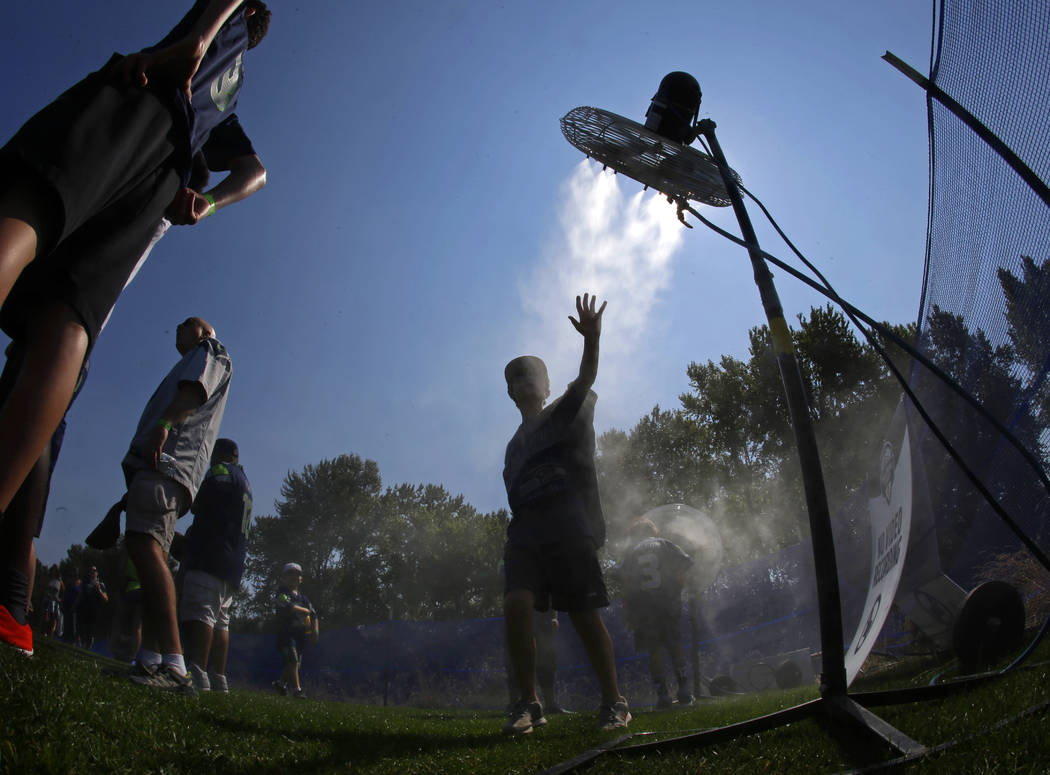 In this Tuesday, Aug. 1, 2017 file photo, a fan attending a Seattle Seahawks NFL football training camp reaches toward a fan as he cools off at a misting station in Renton, Wash., as temperatures ...