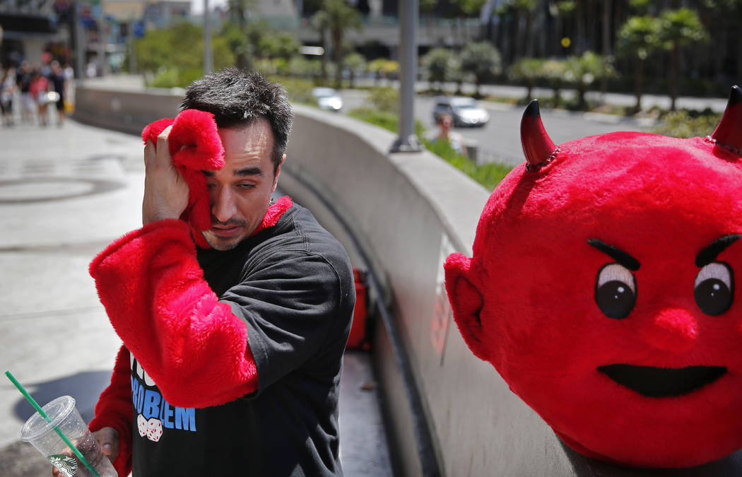 In this July 1, 2015 file photo, Andrew Morales wipes sweat from his face while taking a break from his devil costume in Las Vegas as the western region of the U.S. experiences record heat. (AP Ph ...