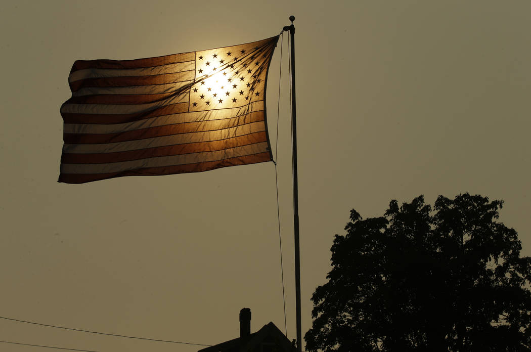 FILE - In this Aug. 2, 2017 file photo, the evening sun shines through a U.S. flag flying in the wind in Tacoma, Wash., against a sky made hazy with smoke from wildfires, as the National Weather S ...