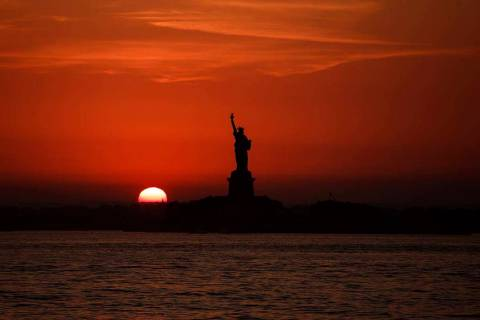 In this July 1, 2018 file photo, the sun sets behind the Statue of Liberty in New York as record high temperatures were recorded over the week in the U.S. and elsewhere. An AP data analysis of rec ...