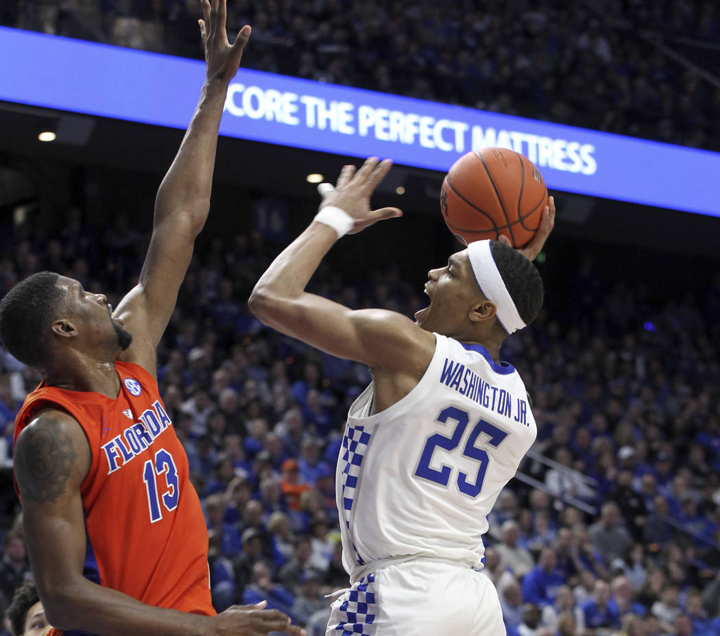 Kentucky's PJ Washington (25) shoots while pressured by Florida's Kevarrius Hayes (13) during the second half of an NCAA college basketball game in Lexington, Ky., Saturday, March 9, 2019. Kentuck ...