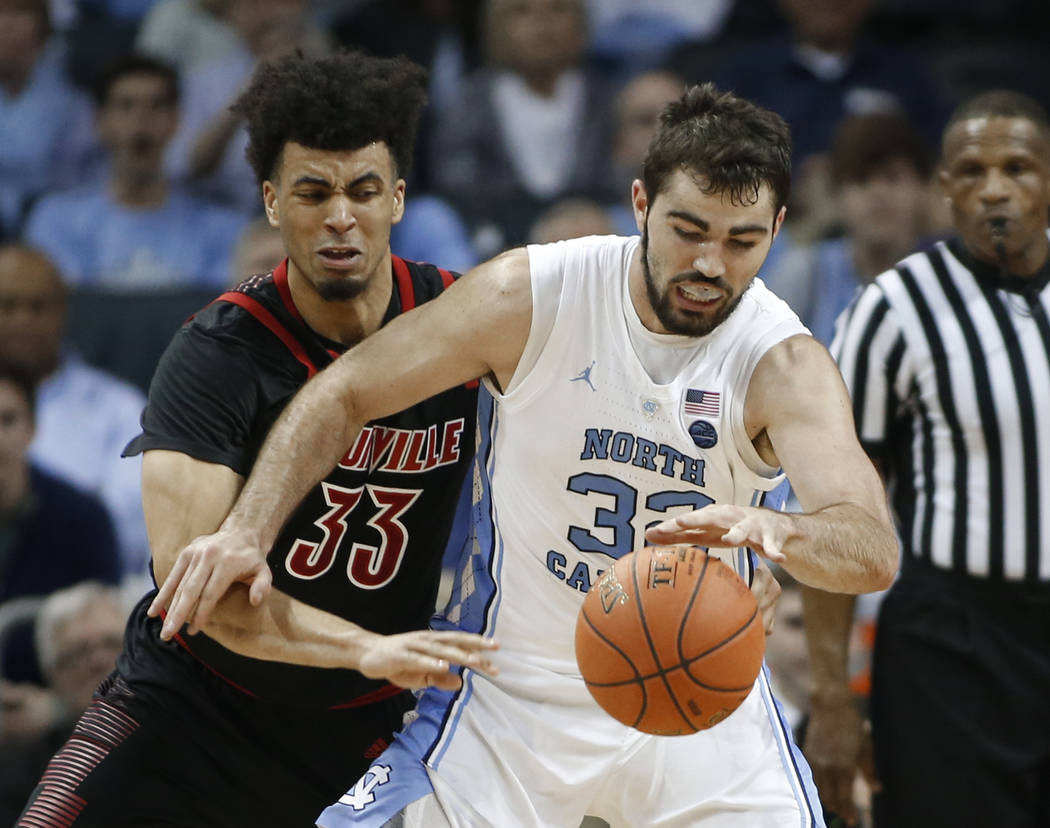 Louisville's Jordan Nwora (33) tries to steal the ball from North Carolina's Luke Maye (32) during the first half of an NCAA college basketball game in the Atlantic Coast Conference tournament in ...
