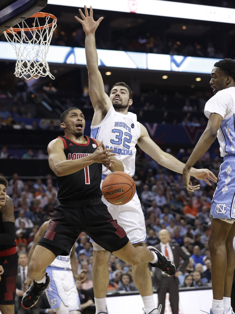 Louisville's Christen Cunningham (1) is fouled as he drives past North Carolina's Luke Maye (32) during the second half of an NCAA college basketball game in the Atlantic Coast Conference tourname ...