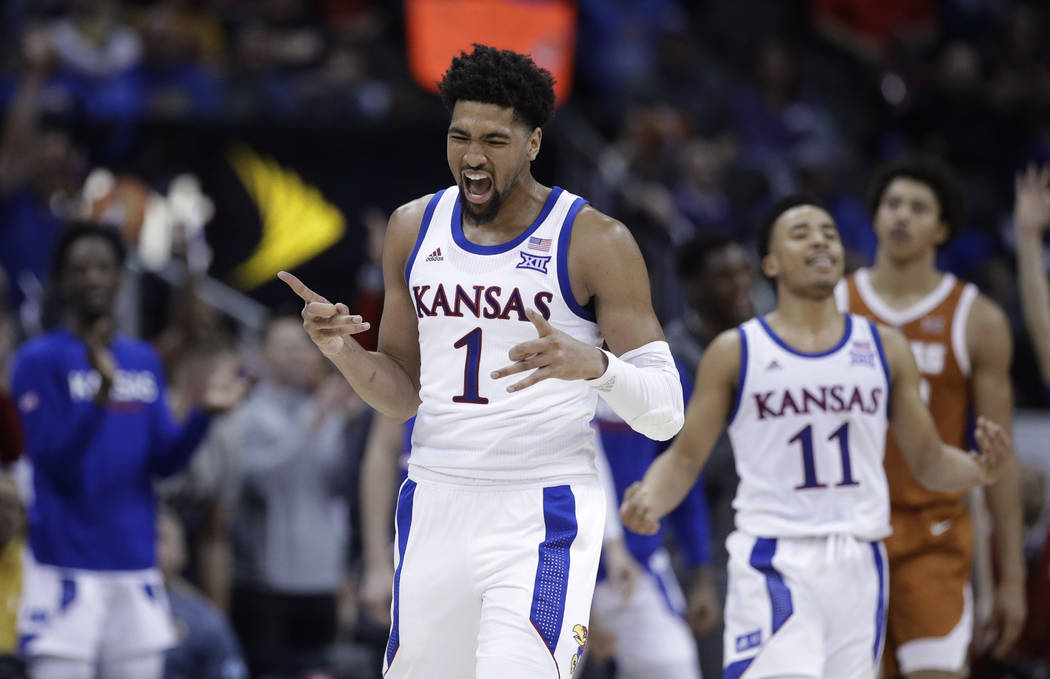 Kansas' Dedric Lawson (1) and Devon Dotson (11) celebrate after Dotson made a 3-point shot during the second half against Texas in an NCAA college basketball game in the Big 12 men's tournament Th ...