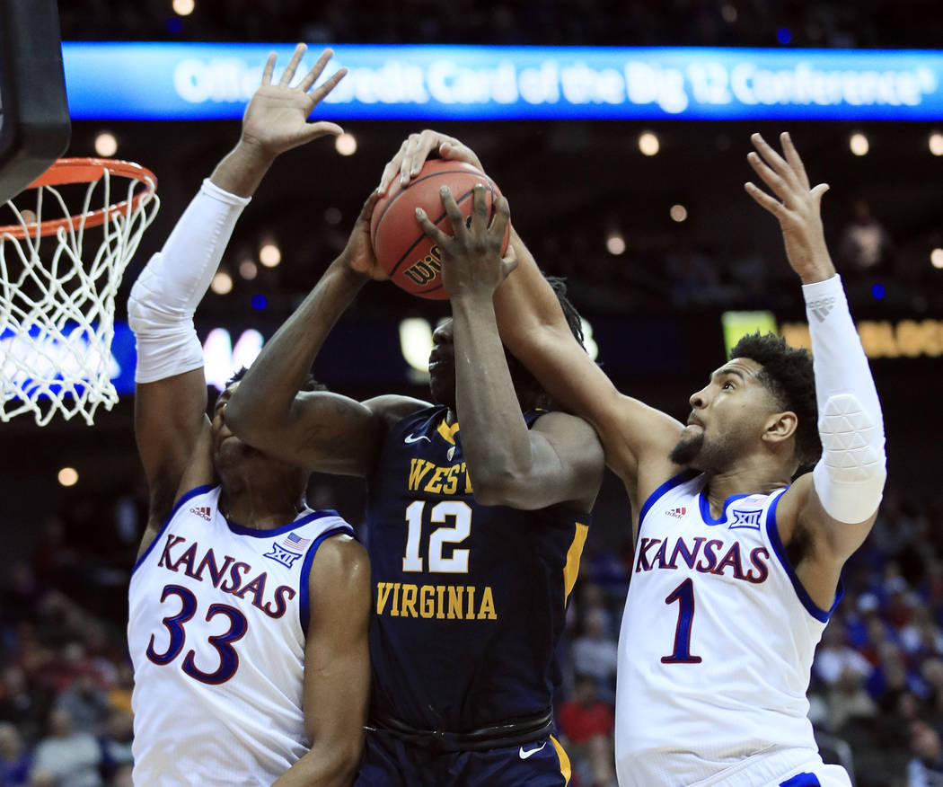 Kansas forward Dedric Lawson (1) blocks a shot by West Virginia forward Andrew Gordon (12) during the second half of an NCAA college basketball game in the semifinals of the Big 12 men's tournamen ...