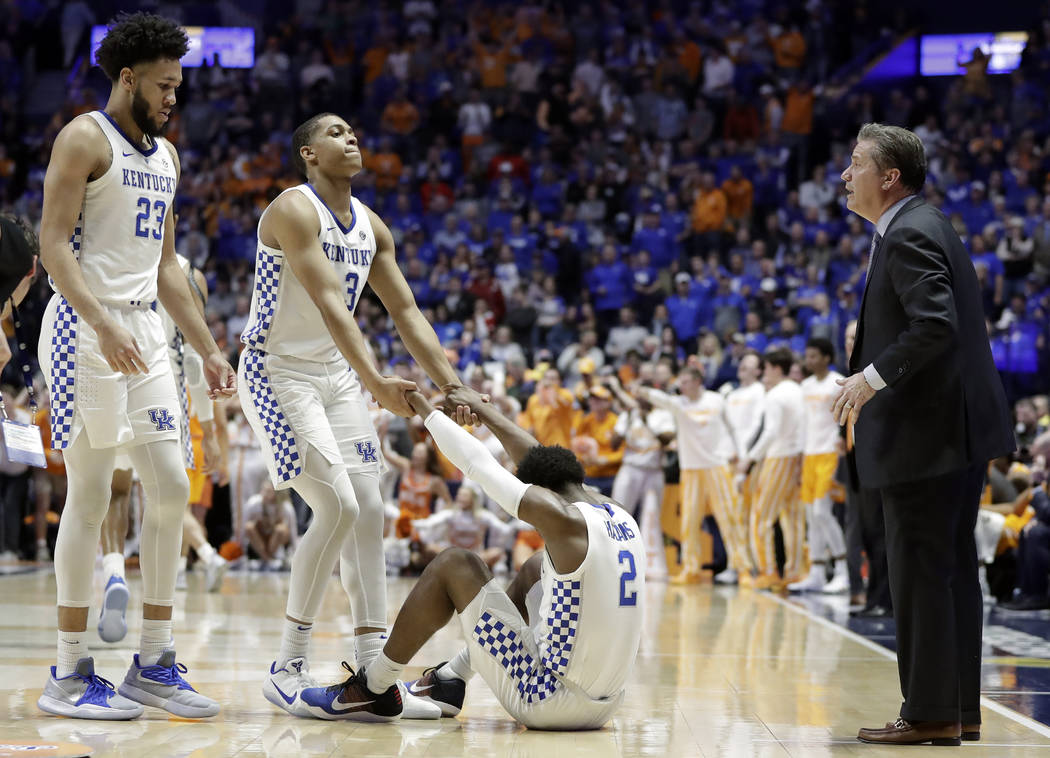 Kentucky guard Ashton Hagans (2) is helped up by Keldon Johnson (3) after Hagans was called for a foul in the final minute of an NCAA college basketball game against Tennessee at the Southeastern ...