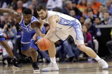 Duke's Zion Williamson, left, and North Carolina's Luke Maye, right, chase a loose ball during the first half of an NCAA college basketball game in the Atlantic Coast Conference tournament in Char ...