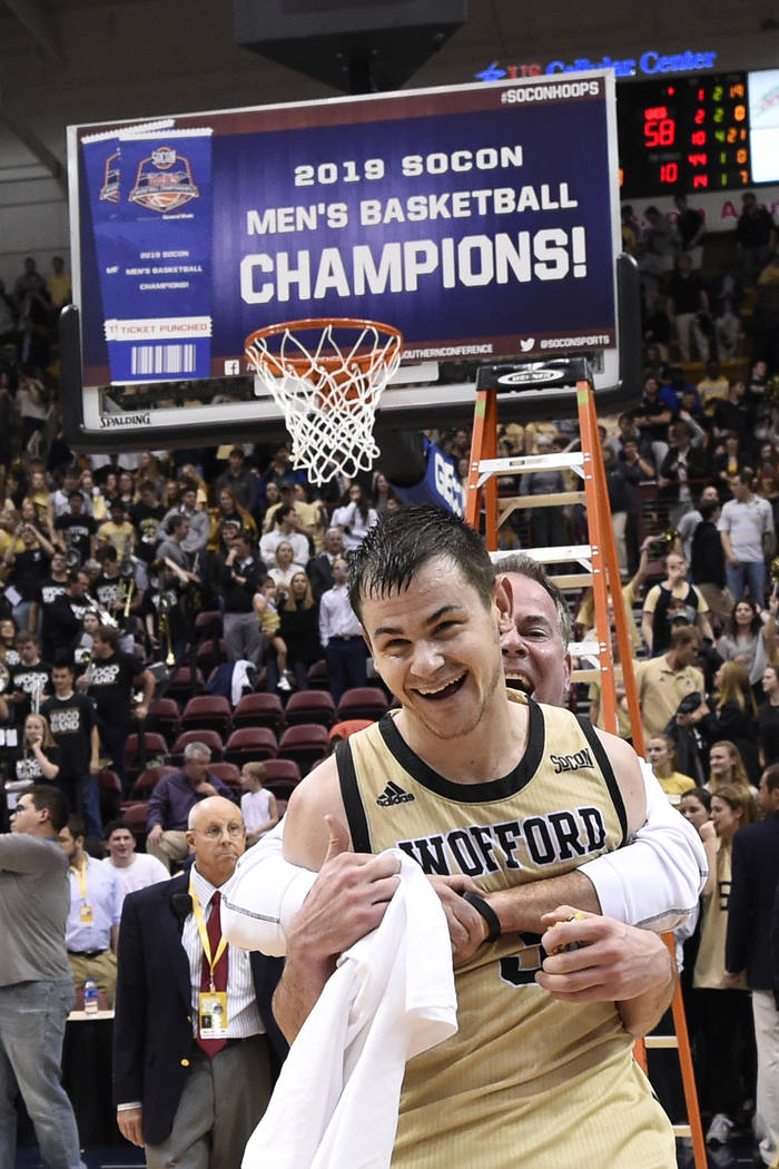 Wofford guard Fletcher Magee (3) receives a hug after his team defeated UNC-Greensboro 70-58 for the Southern Conference tournament championship, Monday, March 11, 2019, in Asheville, N.C. Magree ...