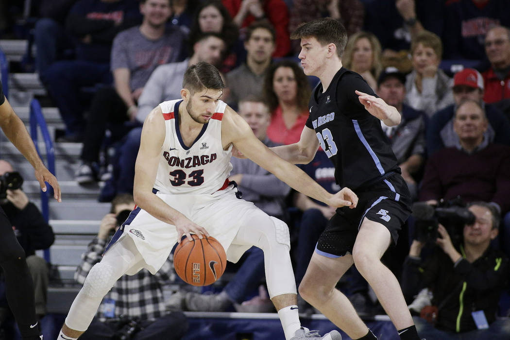 Gonzaga forward Killian Tillie (33) dribbles the ball while defended by San Diego guard Finn Sullivan (23) during the first half of an NCAA college basketball game in Spokane, Wash., Saturday, Feb ...