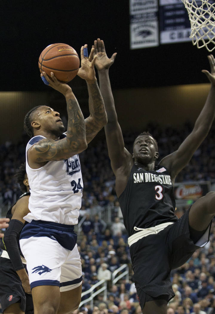 Nevada forward Jordan Caroline (24) drives past San Diego State guard Jeremy Hemsley (42) and guard Jordan Schakel (20) in the second half of an NCAA college basketball game in Reno, Nev., Saturda ...
