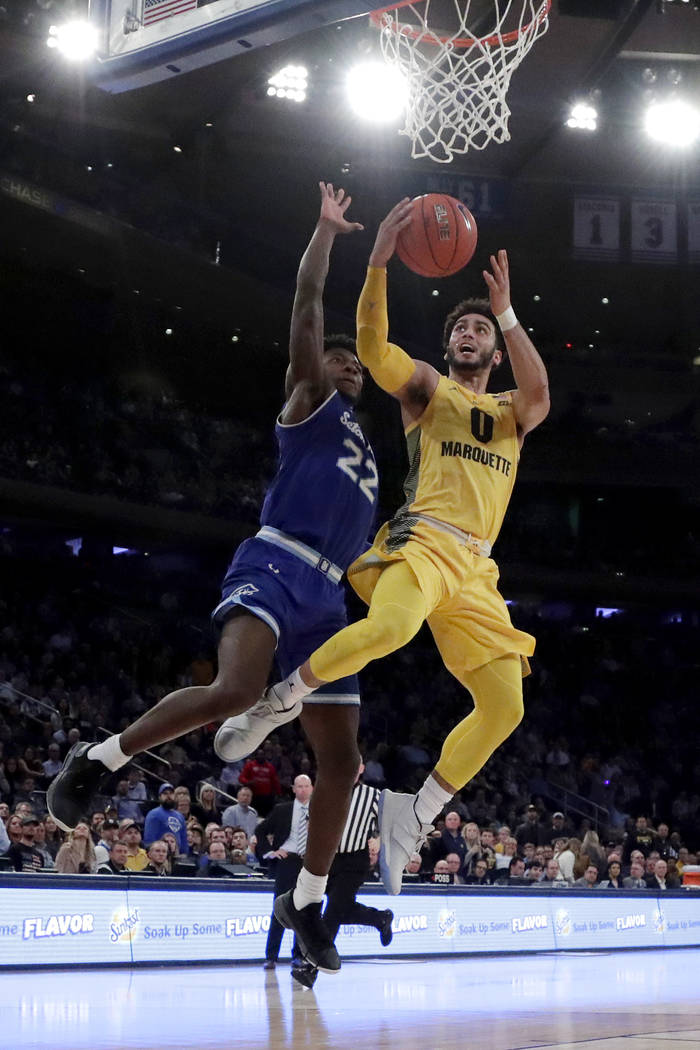 Marquette guard Markus Howard (0) goes up for a shot against Seton Hall guard Myles Cale (22) during the first half of an NCAA college basketball semifinal game in the Big East men's tournament, F ...