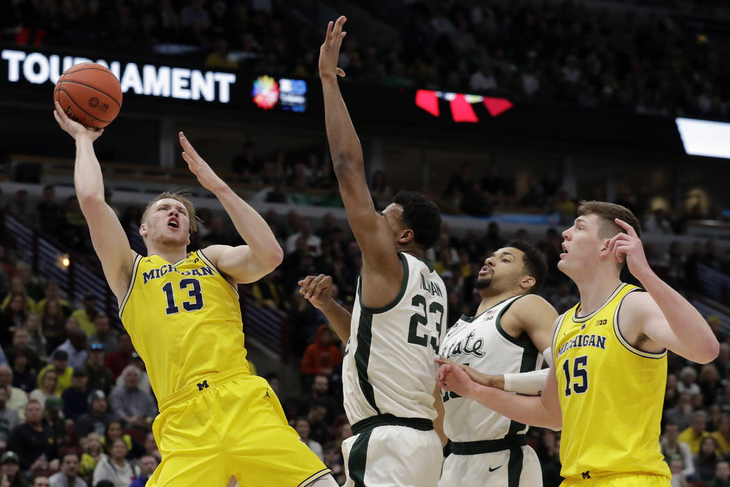 Michigan's Ignas Brazdeikis (13) goes up for a shot against Michigan State's Xavier Tillman (23) during the first half of an NCAA college basketball championship game in the Big Ten Conference tou ...