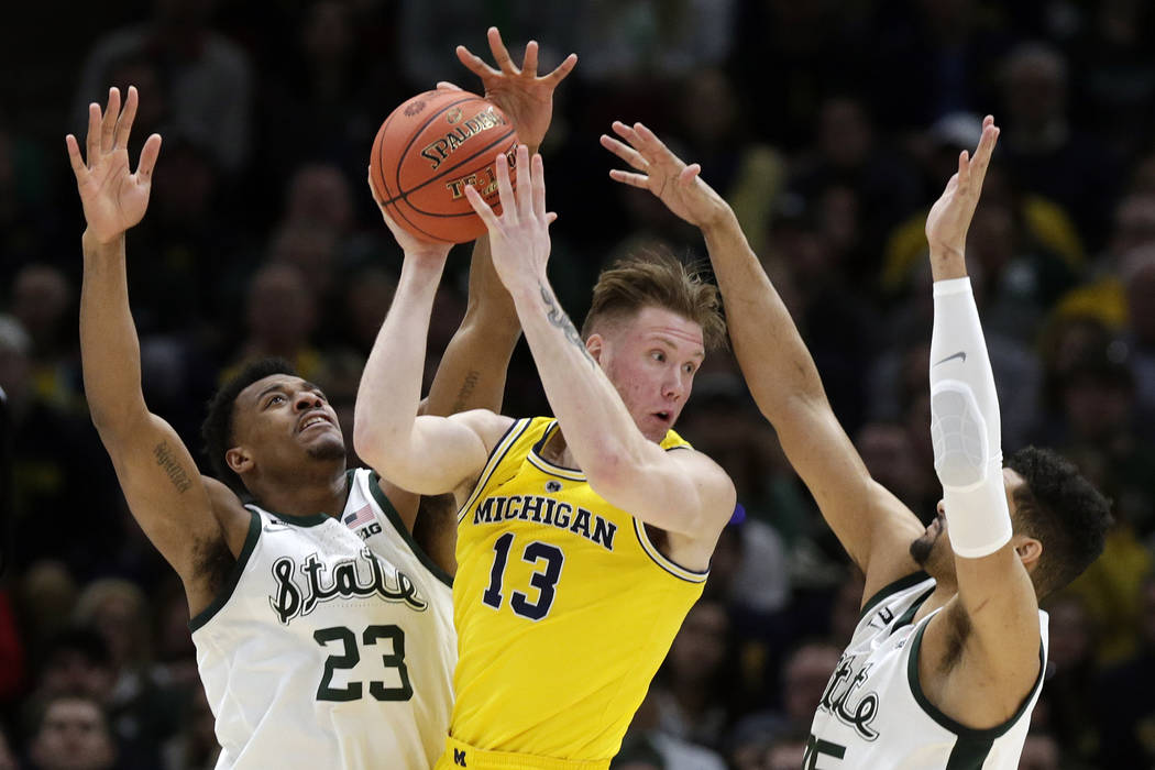 Michigan's Ignas Brazdeikis (13) looks to pass the ball against Michigan State's Xavier Tillman (23) and Kenny Goins (25) during the first half of an NCAA college basketball championship game in t ...