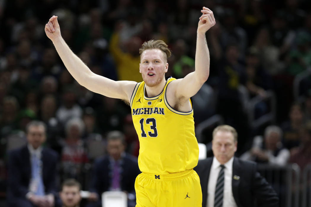 Michigan's Ignas Brazdeikis (13) reacts after shooting a 3-point basket during the first half of an NCAA college basketball championship game against Michigan State in the Big Ten Conference tourn ...