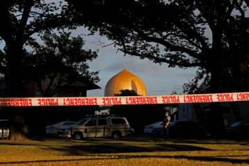 A police officer stands guard in front of the Masjid Al Noor mosque in Christchurch, New Zealand, Sunday, March 17, 2019, where one of two mass shootings occurred. New Zealand's stricken residents ...
