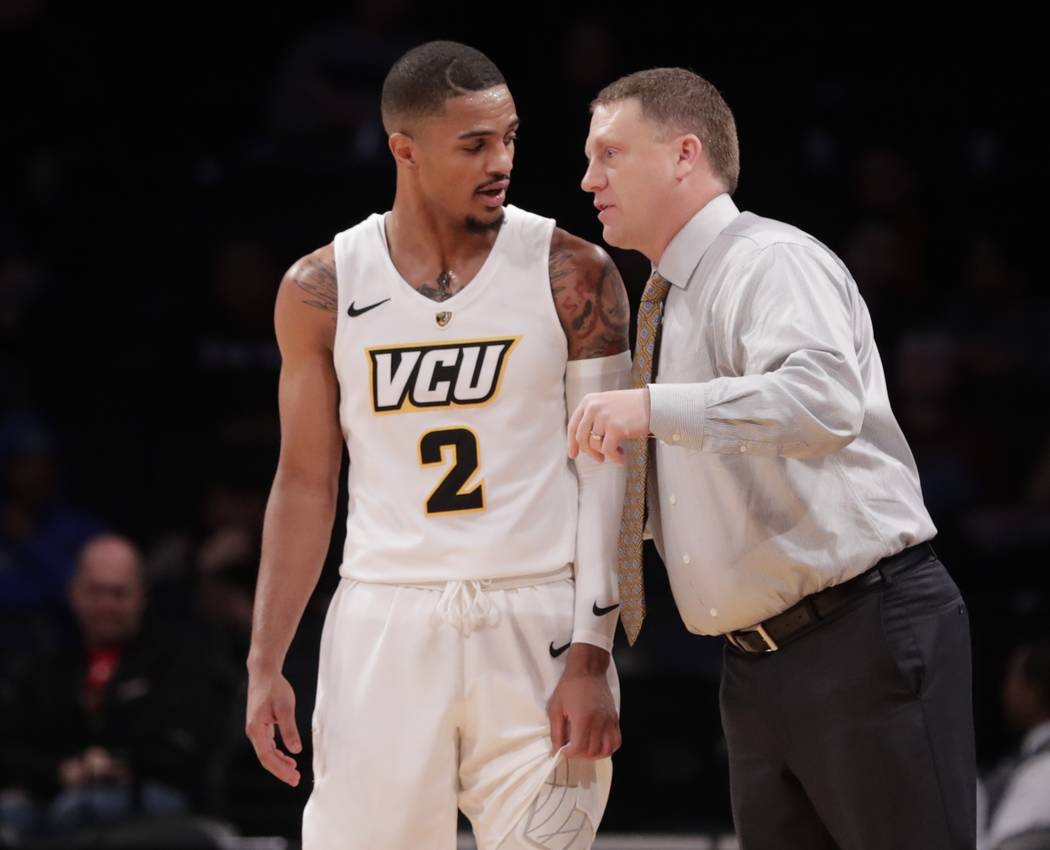 Virginia Commonwealth head coach Mike Rhoades, right, talks to Marcus Evans (2) during the first half of an NCAA college basketball game against Temple in the Legends Classic tournament Monday, No ...