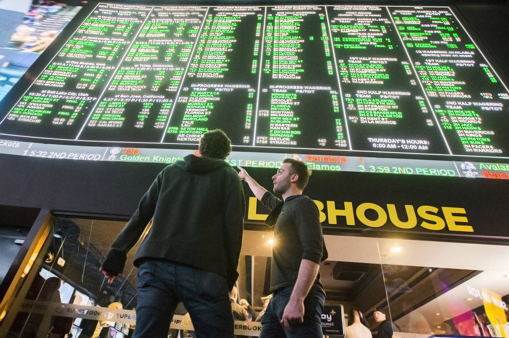 Evan Thoma, right, and Matt Castagna, both from Chicago, Ill., discuss odds during the first day of the NCAA Tournament at the Westgate Sportsbook on Thursday, March 21, 2019, at Westgate, in Las ...