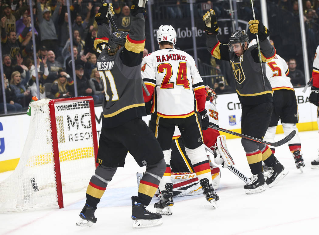 Golden Knights center William Karlsson (71) and right wing Reilly Smith celebrate a goal by defenseman Shea Theodore, not pictured, during the first period of an NHL hockey game at T-Mobile Arena ...