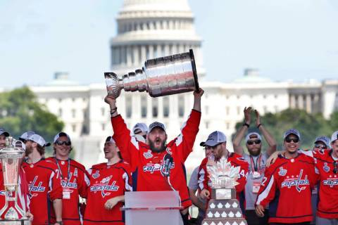 Washington Capitals' Alex Ovechkin holds up the Stanley Cup trophy during the team's Stanley Cup victory celebration at the National Mall in Washington on June 12, 2018. (AP Photo/Jacquelyn Martin ...