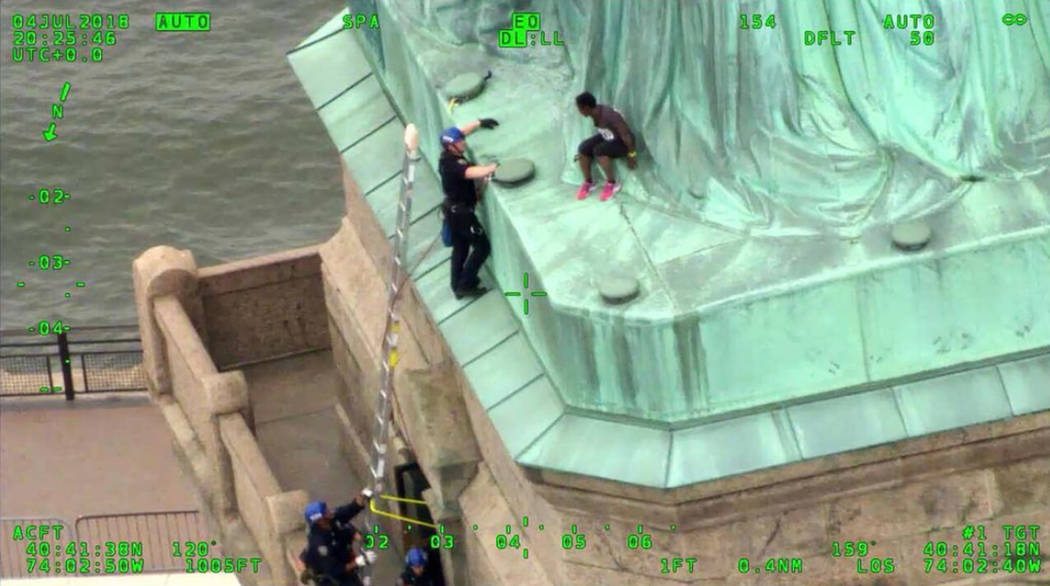 Members of the New York City Police Department Emergency Service Unit work to safely remove Therese Okoumou, a protester who climbed onto the Statue of Liberty and was charged with misdemeanor tre ...