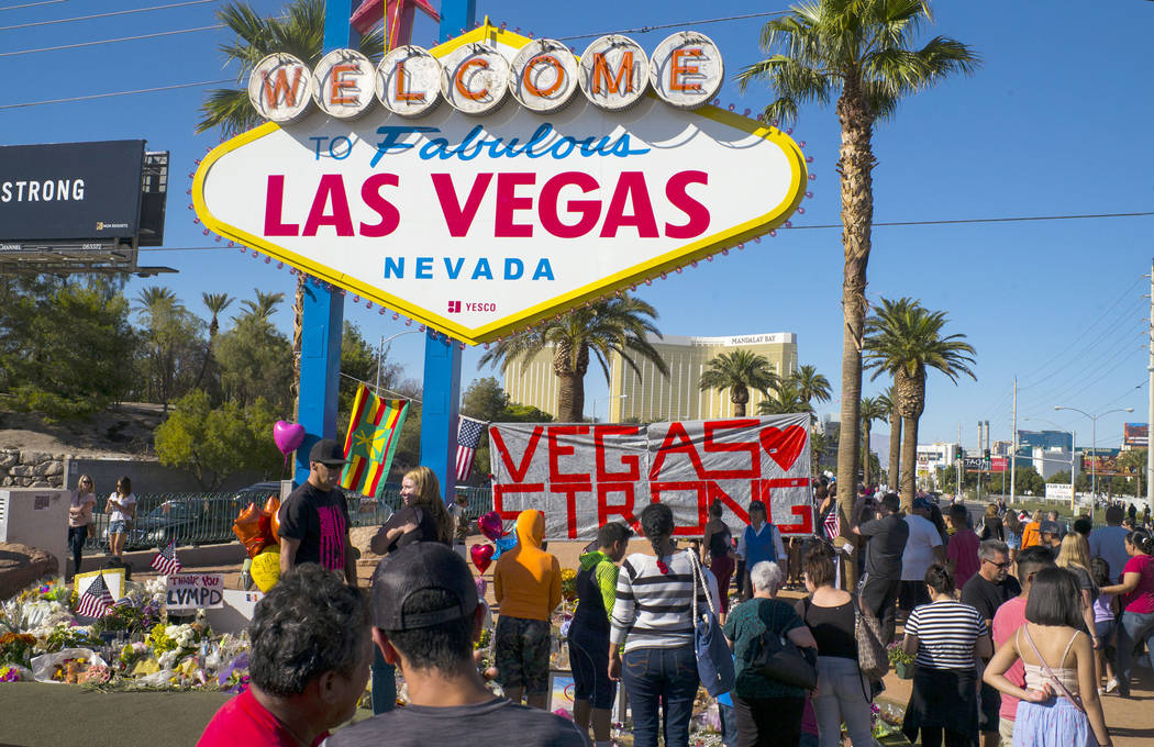 """People visit a makeshift memorial for victims of the Oct. 1 mass shooting near the """"Welcome to Fabulous Las Vegas"""" sign in Las Vegas on Saturday, Oct. 7, 2017. Chase Stevens Las Vegas Review-Journ ..."""