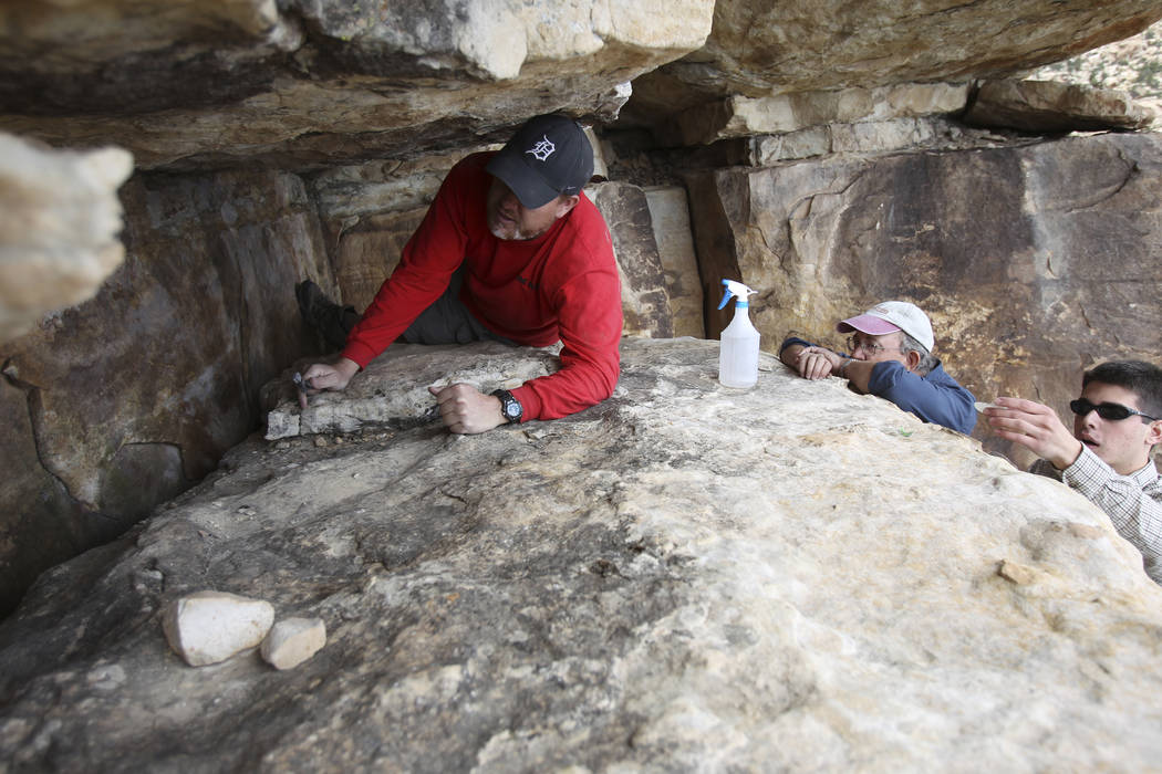 Klaus Cobb, a volunteer with Friends of Red Rock Canyon, left, works Thursday, May 19, 2011, to restore an ancient rock art site in Red Rock Canyon National Conservation Area that was damaged by g ...