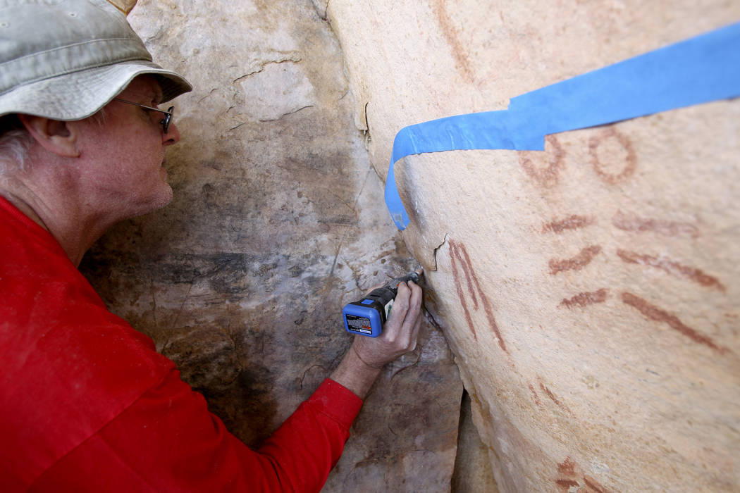 Wyatt Mulvey, a volunteer with Friends of Red Rock Canyon, works Thursday, May 19, 2011, to restore an ancient rock art site near Lost Creek that was damaged by graffiti vandals in November. (K.M ...