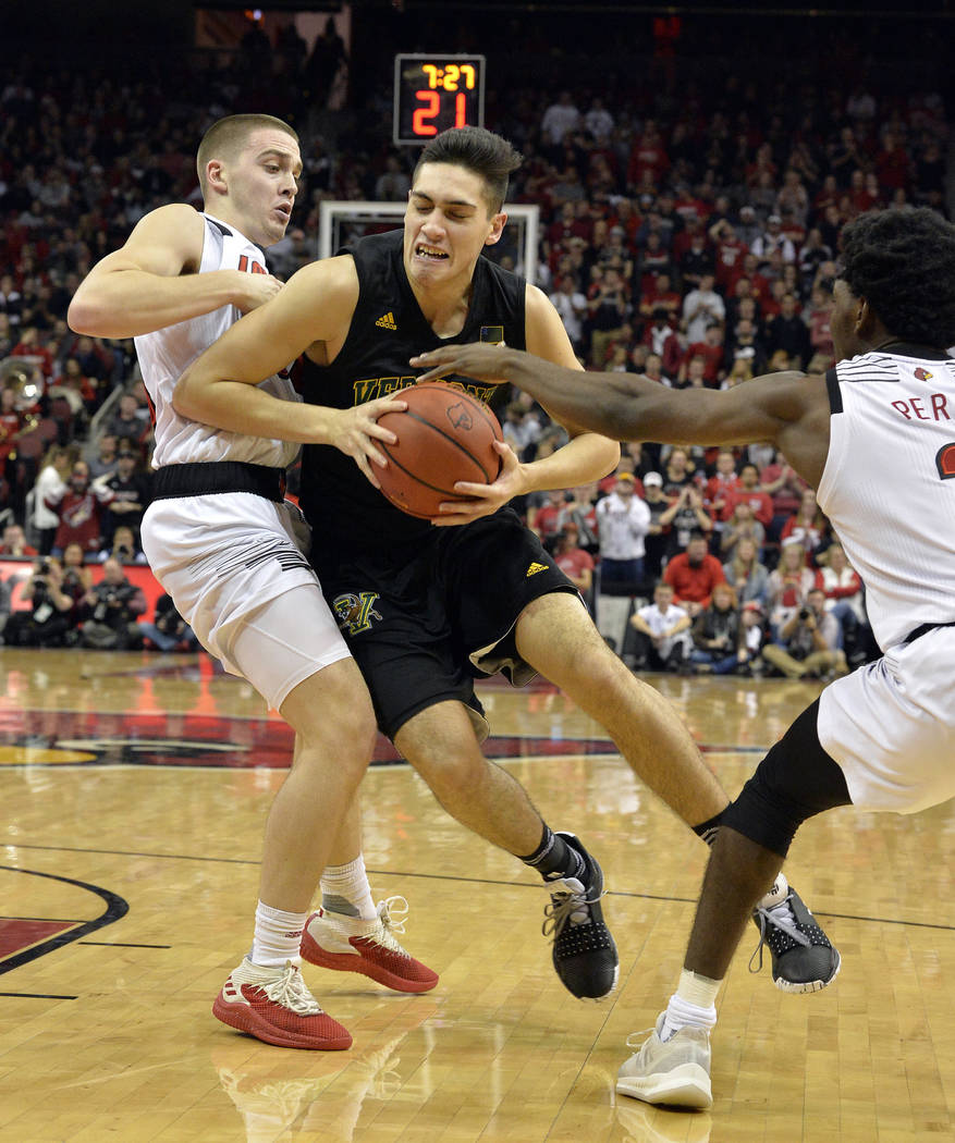 Vermont guard Robin Duncan (4) attempts to drive between Louisville guard Ryan McMahon, left, and guard Darius Perry during the first half of an NCAA college basketball game in Louisville, Ky., Fr ...
