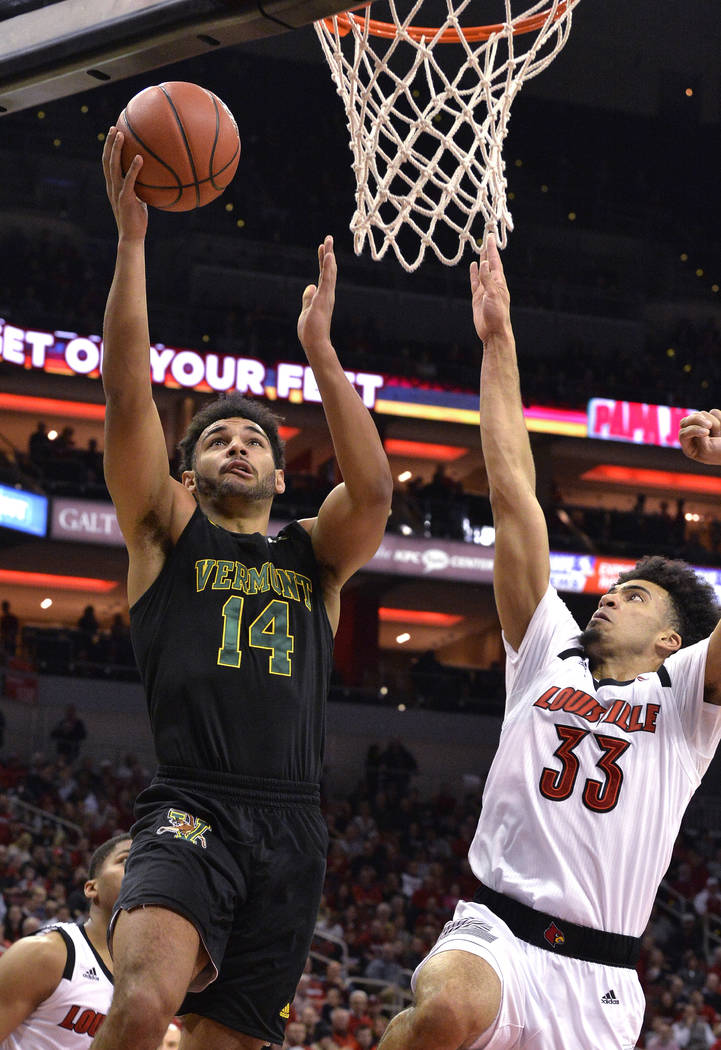 Vermont forward Isaiah Moll (14) shoots as Louisville forward Jordan Nwora (33) defends during the first half of an NCAA college basketball game in Louisville, Ky., Friday, Nov. 16, 2018. (AP Phot ...