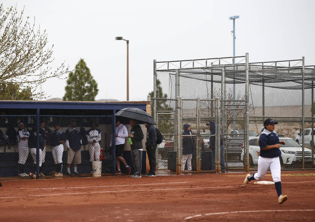 Shadow Ridge players keep cover from rain in the dugout as a softball game against Centennial is delayed at Shadow Ridge High School in Las Vegas on Wednesday, March 20, 2019. (Chase Stevens/Las V ...