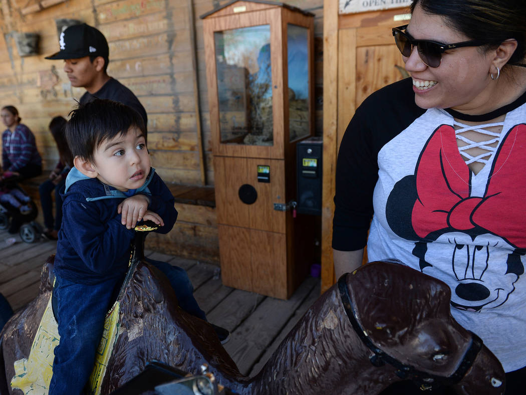 Jonsito Lakins, 2, from Las Vegas sits on a toy camel as he looks at his mother, Karen Lakins, during the last day of operations at Bonnie Springs Ranch in Las Vegas, Sunday, March 17, 2019. (Caro ...